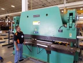 A SFMS team member inspects an accupress machine